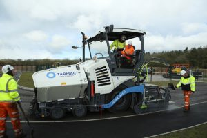The Duke of Cambridge (seated in cab) operating an asphalt paver during a visit to the Tarmac National Skills and Safety Park in Nottinghamshire.
