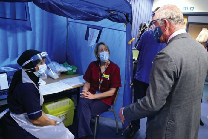 The Prince of Wales meets with front line health and care workers administering and receiving the Covid-19 vaccine during a visit to the Gloucestershire Vaccination Centre at Gloucestershire Royal Hospital.