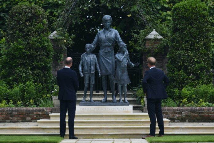 The Duke of Cambridge and Duke of Sussex look at a statue they commissioned of their mother Diana, Princess of Wales, in the Sunken Garden at Kensington Palace, London.